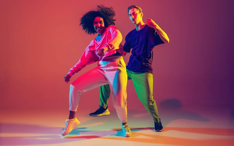 Stylish men and woman dancing hip-hop in bright clothes on gradient background at dance hall in neon light