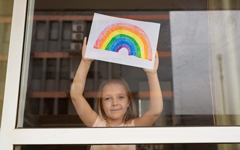 kid-looking-through-window-with-painted-rainbow-du-CLEH8S4